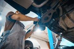 Reparatur- und Kontrollauto in der Reparaturwerkstatt Ein erfahrener Techniker repariert das fehlerhafte Teil des Autos Ich ?nder lizenzfreies stockbild