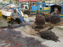 Reparatur von Fischernetzen im Hafen malta Marsachlokk stockfotos