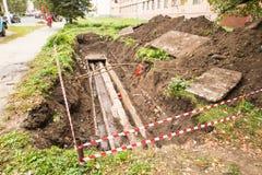 Reparatur von Untertagekommunikationen, von Wasser und von Warmwasserleitungen auf der ruinierten Pflasterung Stockfoto