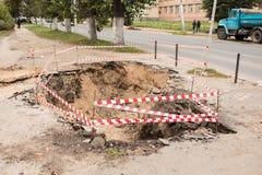 Reparatur von Untertagekommunikationen, von Wasser und von Warmwasserleitungen auf der ruinierten Pflasterung Stockbilder