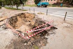 Reparatur von Untertagekommunikationen, von Wasser und von Warmwasserleitungen auf der ruinierten Pflasterung Stockbild