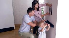 Reparaturen im flachen, netten Kinderjungen hilft Eltern, Regal an Wand nach Verlegung in der Wohnung wegzulaufen stock video footage