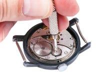 Reparaturhauer repariert alte Uhr auf Weiß Stockbilder
