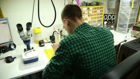Reparaturwerkstatt führt Reparatur von Smartphones durch stock footage