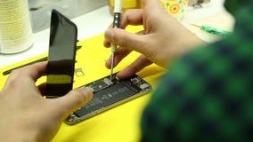 Reparaturwerkstatt f?hrt Reparatur von Smartphones durch stock video footage