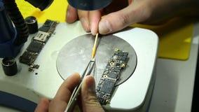 Reparaturwerkstatt f?hrt Reparatur von Smartphones durch stock footage