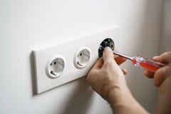 Repare al hombre del zócalo de la electricidad con las manos limpias Seguridad o reparación incorrecta del mercado eléctrico imagenes de archivo
