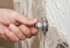 Repare el grifo del soporte de la pared, vueltas del fontanero de la mano del primer excéntricas fotos de archivo libres de regalías
