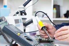 Repare los dispositivos electrónicos, soldando piezas Fotografía de archivo libre de regalías