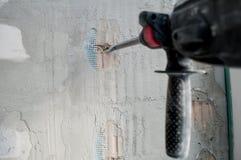 Repare o conceito, ferramentas do reparo, trabalhador do construtor com a broca de martelo bonde que faz o furo na parede no apar foto de stock royalty free