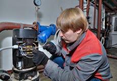 Repare o sistema de aquecimento da bomba, mecânico conecta fios a bonde Imagens de Stock Royalty Free