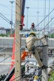 Repare un cable en los posts de la electricidad Foto de archivo libre de regalías