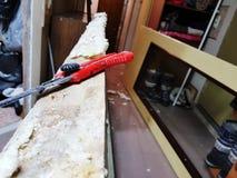 Repare - un cuchillo de la construcción en la canillera de puerta con espuma del montaje imagenes de archivo