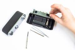 Reparera av den gamla kameran genom att använda skruvmejseln Arkivfoto