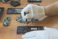 Reparera den skadade mobiltelefonmobilen av teknikeren i vita handskar endast händer på det synliga skrivbordet Royaltyfri Fotografi