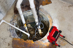 Reparera en latringroppump i en källare Arkivbild