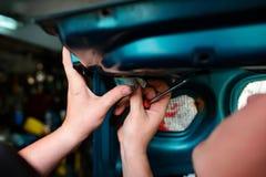 Reparera för Closeup av en bruten blå bil i garage vid händer av machanic arkivbild