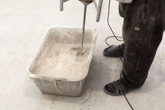 Reparieren Sie Arbeit Strömende Böden im Raum Füllen Sie Tiradenbodenreparatur und versorgen Sie Konkreter Mischer des Arbeitskra Stockbilder