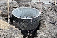 Reparieren Sie Arbeit und konkrete Kreise für die gut herein Grube Stockbild