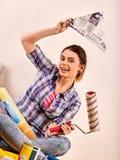 Reparieren Sie die Hauptfrau, die Farbenrolle für Tapete hält Lizenzfreie Stockfotografie