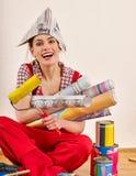 Reparieren Sie die Hauptfrau, die Farbenrolle für Tapete hält Lizenzfreie Stockbilder