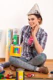 Reparieren Sie die Hauptfrau, die Farbenrolle für Tapete hält Lizenzfreies Stockbild