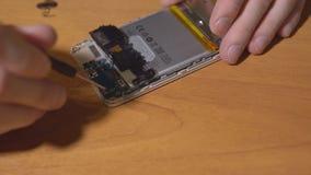 Reparieren Sie einen Handy auf einer braunen Tabelle stock video