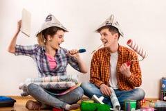 Reparieren Sie Familie durch Gebäudehaus des glücklichen Paars unter Verwendung des Geistniveaus, um zu messen Stockfotografie