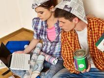 Reparieren Sie Familie durch Gebäudehaus des glücklichen Paars unter Verwendung des weißen Laptops Lizenzfreie Stockfotos
