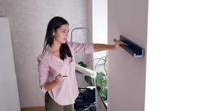 Reparieren Sie Wohnung, tut reizende Frau das Neu streichen und hängt Regal auf Wand während der Erneuerung des Hauses stock video