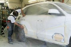 reparing在汽车修理店的技工一辆汽车 图库摄影