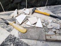 Reparo - a construção com ferramentas martela, malho, talhador e uma faca com os estilhaços da telha imagem de stock