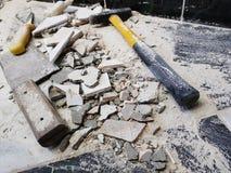 Reparo - a construção com ferramentas martela, malho, talhador e uma faca com os estilhaços da telha imagens de stock