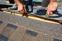 Reparo de um telhado das telhas O feltro ou o betume do telhado do corte do Roofer durante waterproofing trabalham Telhas do telh Imagens de Stock