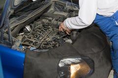 Reparo do carro O mecânico fixa o motor de um carro Fotografia de Stock Royalty Free