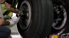 Reparo do freio dos aviões Feche acima da roda e do eixo do avião Pneumático enorme do avião com eixo e trem de aterrissagem do p video estoque