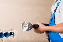 Reparo do furo de perfuração do trabalhador da construção na casa, disposição, com imagem de stock