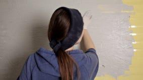 Reparo home A menina espalha o emplastro na parede com uma grande espátula do metal para alinhar o enchimento do emplastro na par video estoque