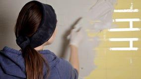 Reparo home A menina espalha o emplastro na parede com uma grande esp?tula do metal para alinhar o enchimento do emplastro na par filme