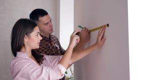 Reparo, jovem mulher e homem do apartamento com a fita métrica à disposição que faz a renovação nos novos domicilios video estoque
