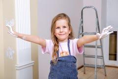Reparo no apartamento A mãe e a filha felizes da família nos aventais pintam a parede com pintura branca A menina mostra-lhe as p imagem de stock royalty free