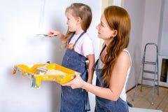 Reparo no apartamento A mãe e a filha felizes da família nos aventais pintam a parede com pintura branca a filha pinta a parede fotografia de stock royalty free