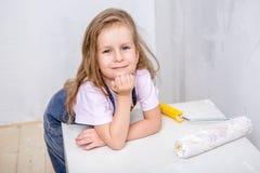 Reparo no apartamento A mãe feliz da família e a filha pequena em aventais azuis pintam a parede com pintura branca A menina tomo fotografia de stock