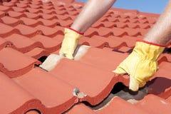 Reparos de telhado da telha do trabalhador da construção Fotos de Stock