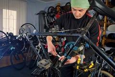 Reparos mestres da bicicleta na oficina 3 Fotos de Stock Royalty Free