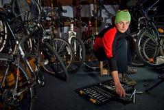 Reparos mestres da bicicleta na oficina Fotos de Stock Royalty Free