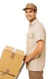 Repartidor joven sonriente con las cajas de cartón fotografía de archivo
