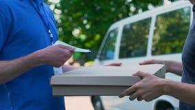 Repartidor que recibe el dinero para la pizza que transporta, entrega de la comida, trabajo a tiempo parcial almacen de metraje de vídeo