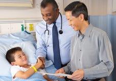 Reparto dei dottori Visiting Child Patient On Immagini Stock