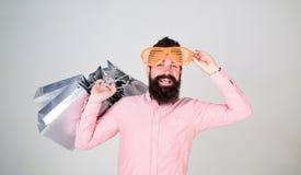 Reparto provechoso Cómo conseguir listo para sus vacaciones próximas Inconformista barbudo del hombre con los bolsos de compras d imagenes de archivo